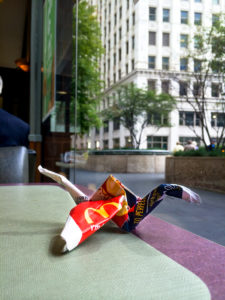 Origami made from fast food paper bag sitting on table at McDona