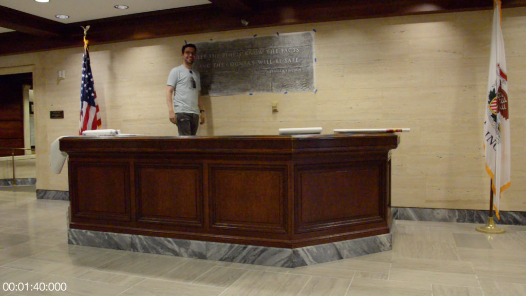 Matt Maldre standing next to pencil rubbing of quote in Tribune Tower lobby