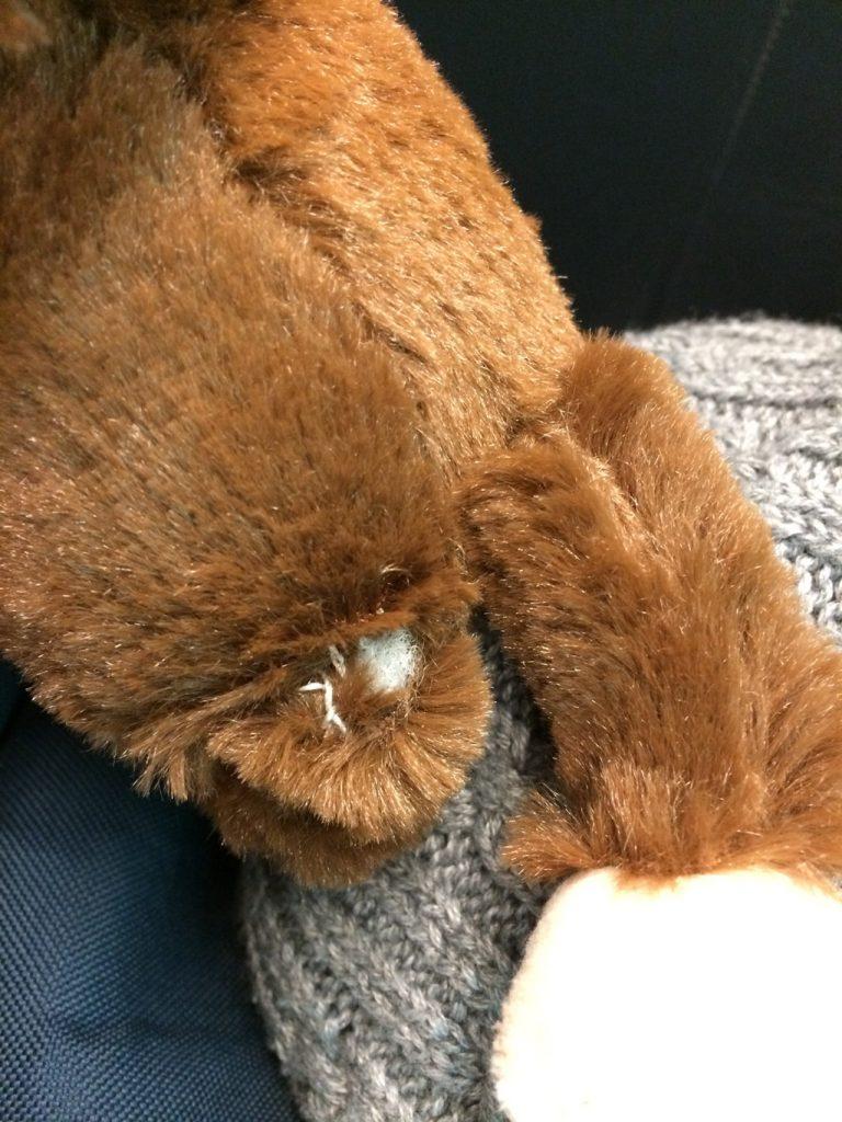 Plush monkey with ripped leg