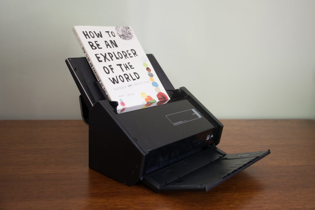 "The book ""How to be an Explorer of the World"" sitting in a document scanner"