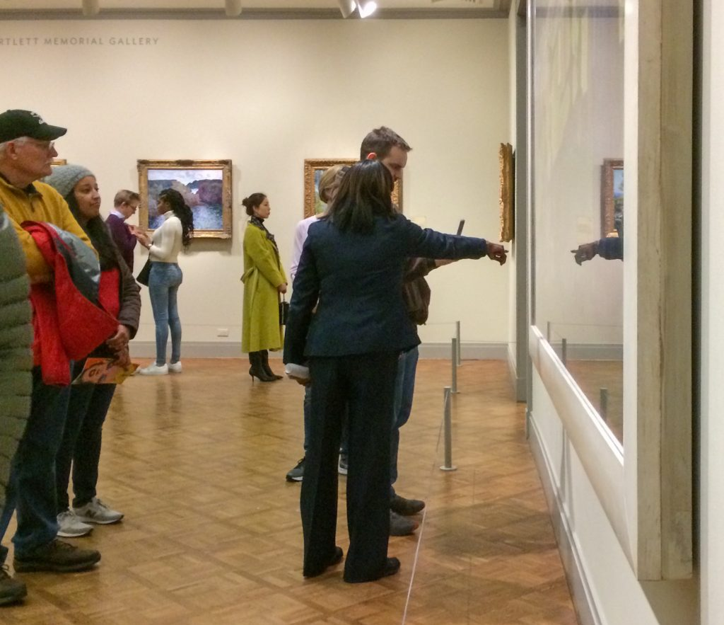 "Art museum security guard pointing out details in ""A Sunday on L"