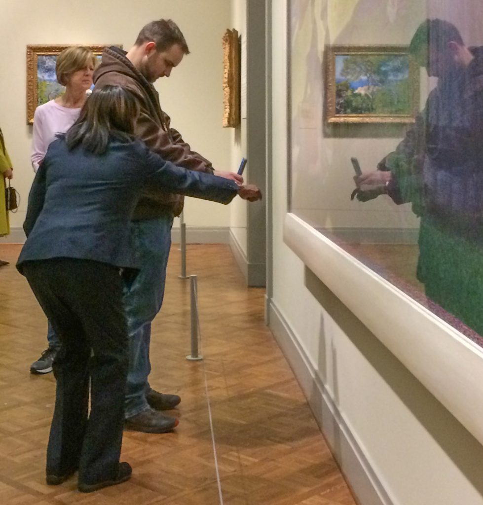 Security guard indicates something interesting to a museum patron