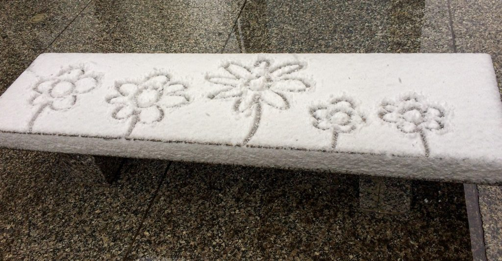 Drawing of flowers in snow on public bench