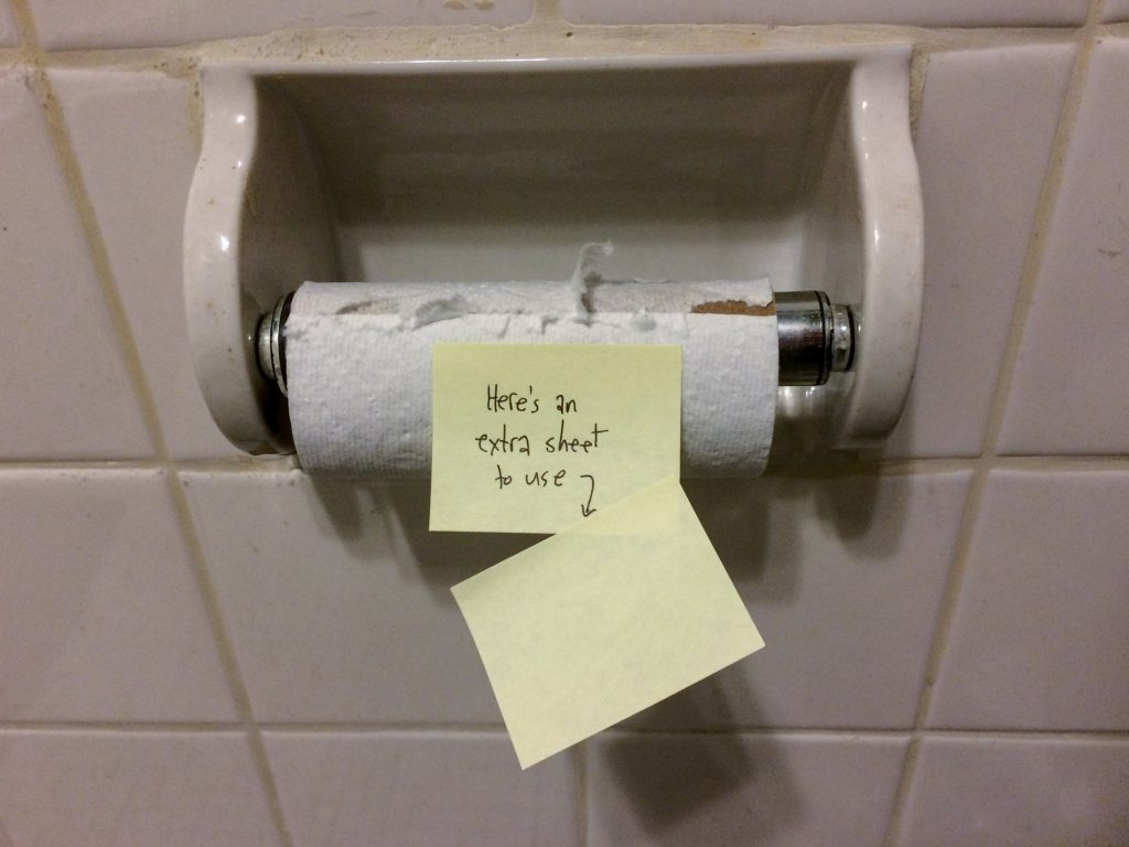 "An empty toilet paper roll hanging in the bathroom. A sticky note is attached with the words ""Here's an extra sheet to use"""