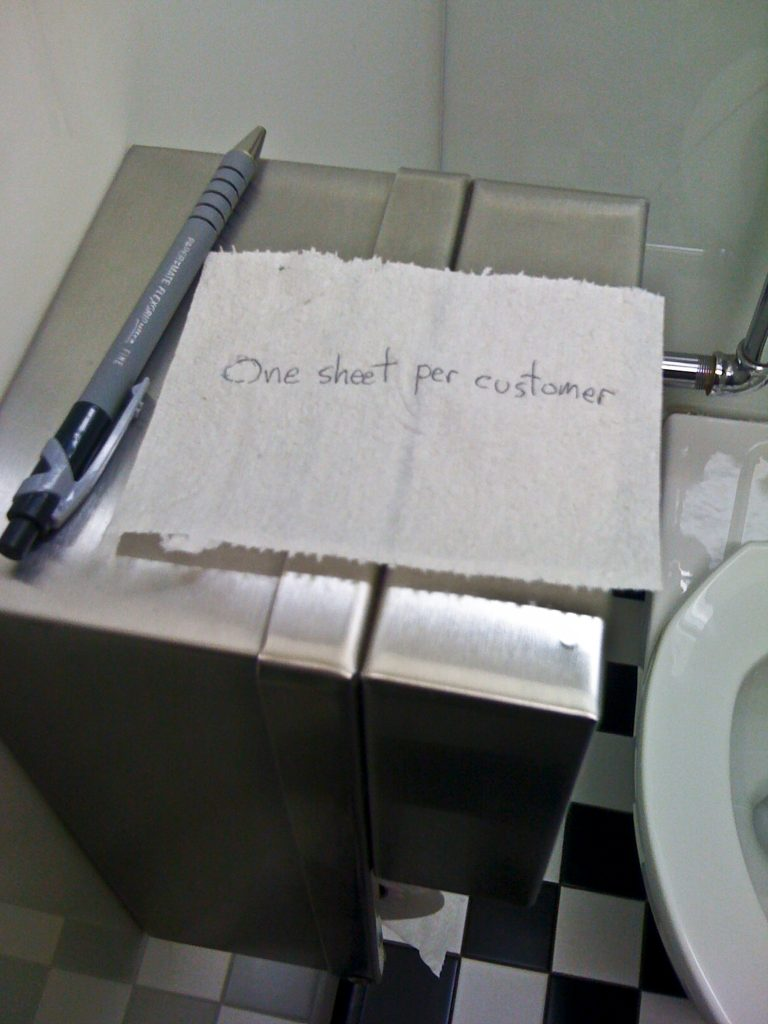 "A single sheet of toilet paper, with the words ""One sheet per customer"" written on the sheet."