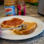 Use a spoon to spread jelly and peanut butter