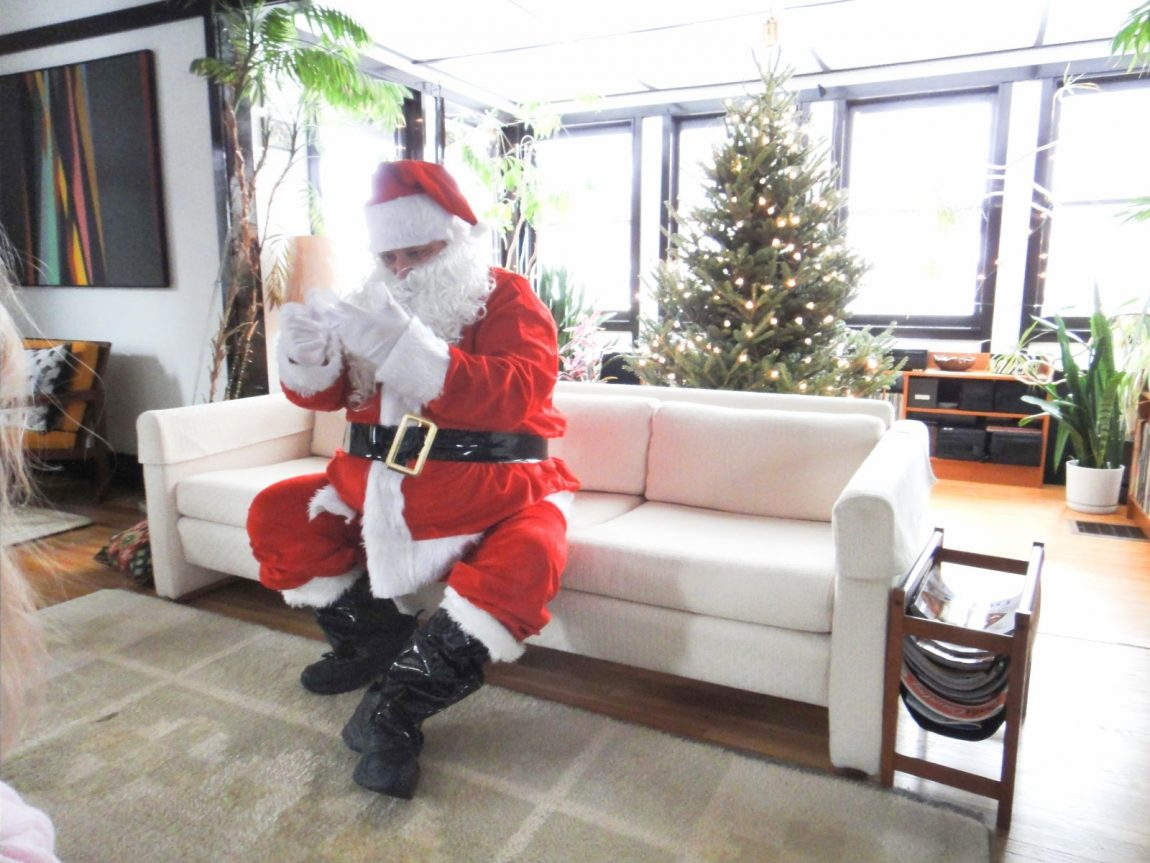 Grandpa dressed up as santa claus sitting on couch