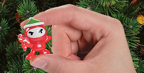 Christmas ninja held by hand in front of Christmas tree