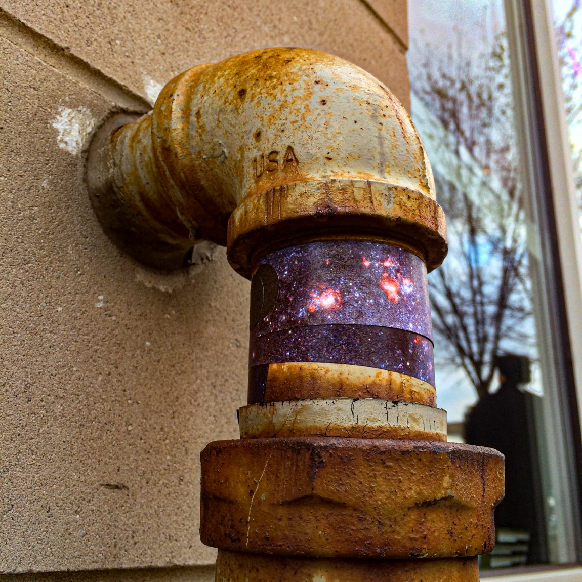 M74 Spiral Galaxy wrapped around water pipe outside The Book Cellar bookstore