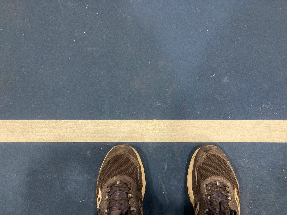 Photo of my feet by the foul line for the tennis courts in DuPage County Fairgrounds
