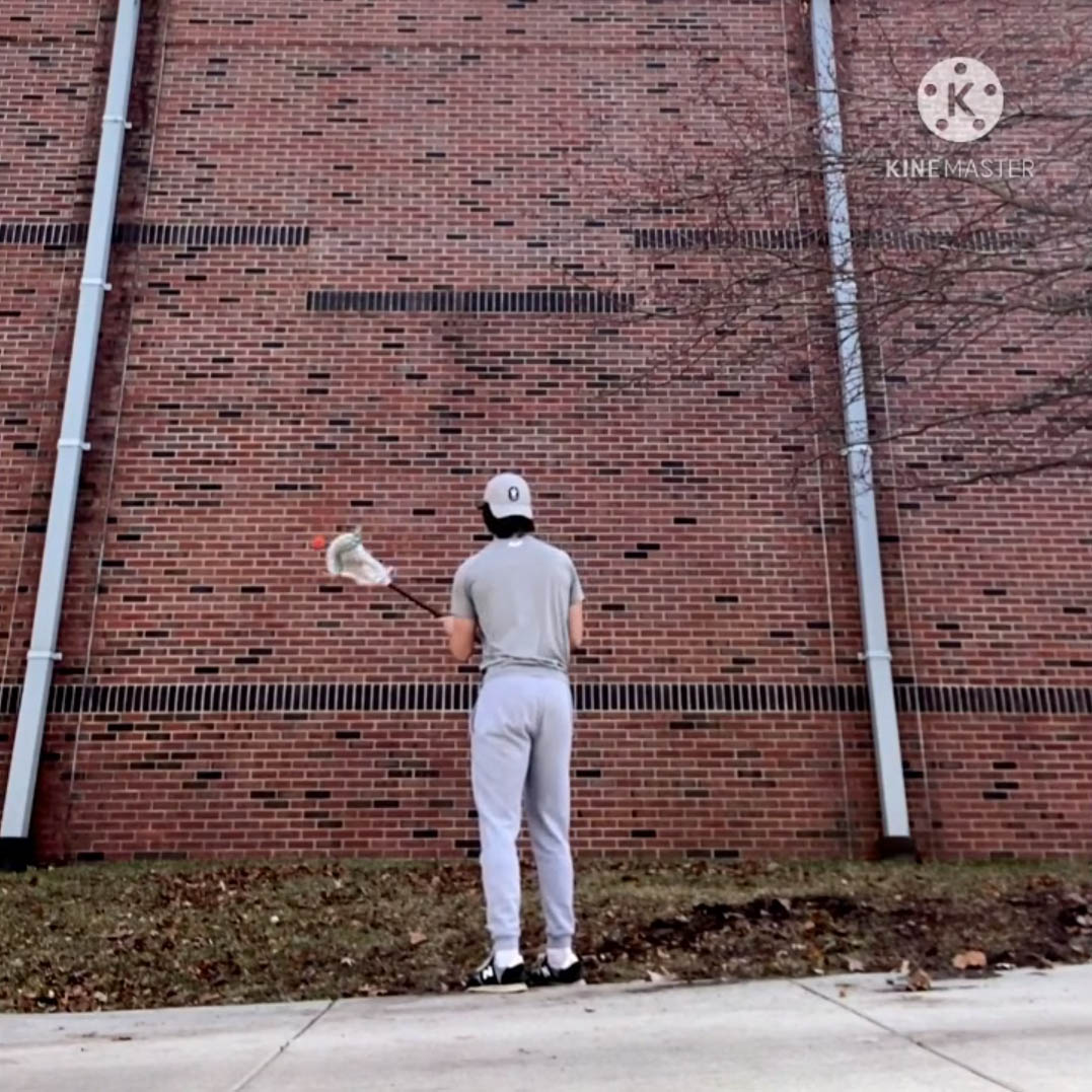 Man throws lacrosse ball against large wall at IWU